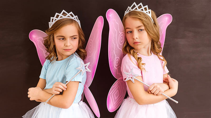 image shows two young girls dressed as fairies with their arms crossed and their backs to one another looking angry