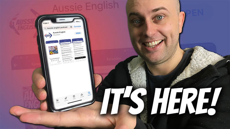 """image shows pete smissen holding a phone showing the aussie english application with the text """"it's here"""" below"""