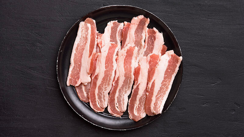 image shows a plate of uncooked bacon on a table