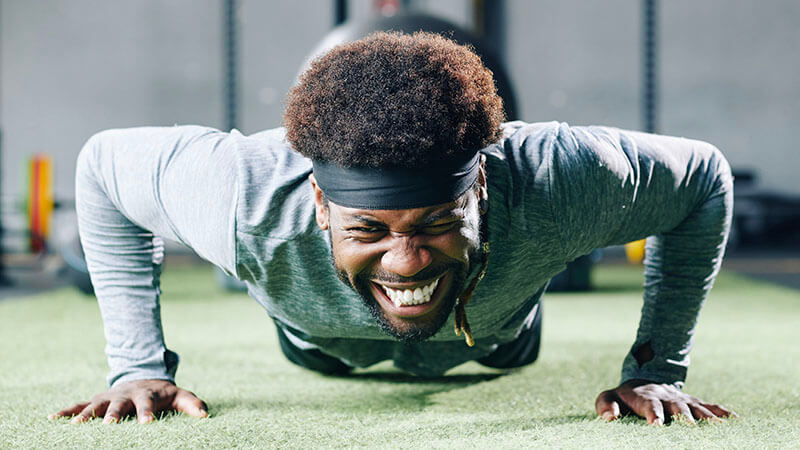 image shows a man in the push up position exerting a lot of effort