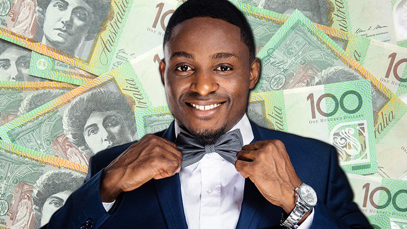 images shows a handsome black man in a suit pulling at his bow tie with australian $100 bills behind him
